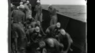 Imperial Japanese Navy sailors scrub the decks of their warship before their landing force goes ashore on the Cinatuna Island and discovers a burned...