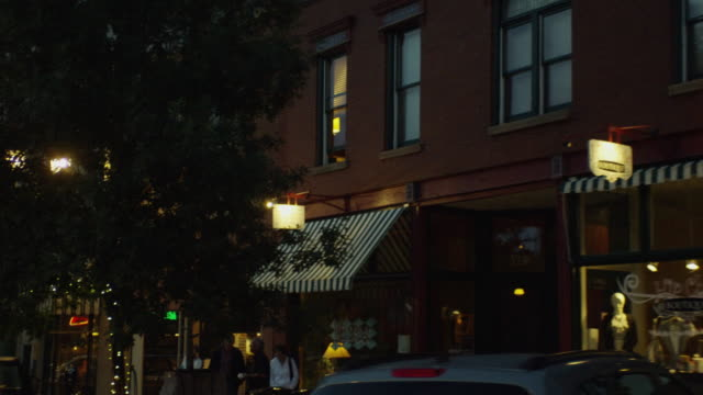 In early evening light, the camera moves along a quaint US main street with illuminated shops and street lights
