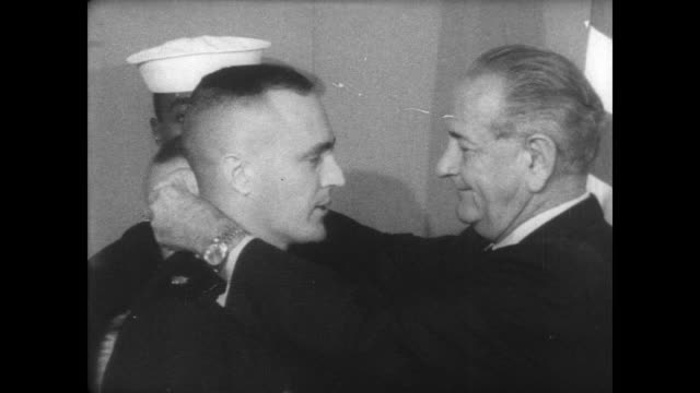 In East Room of White House President Lyndon B Johnson pins medal of honor on chest of Marine Major Howard Lee / shakes hands / CU Lee's son and...