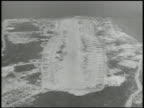 In flight over island WS Angaur Island airfield WS TRACKING Bomber group passing AERIAL TD Consolidated B24 'Liberator' heavy bomber in flight TD WS...
