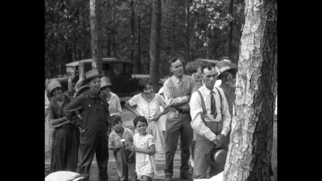 In Malvern AR US Commerce Secretary Herbert Hoover sits at corner of log cabin porch / residents lined up in pine forest / Hoover and state flood...