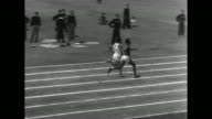 In Olympic Stadium start of men's 400meter run at Bolivarian Games / CU hand holding stopwatch / runners come around last turn and head down final...