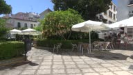 In Plaza de Flores Estepona with people eating and drinking in cafe in background and two girls walking across the WS Datura are also known as...