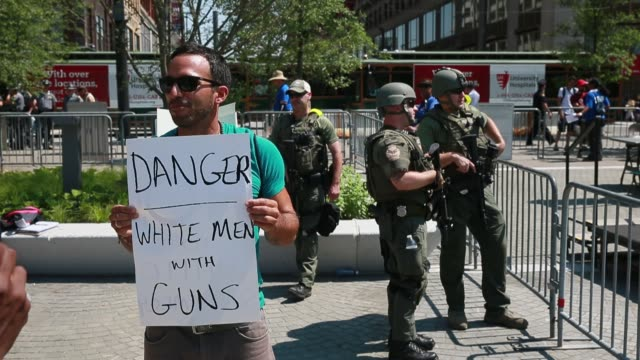In Public Square a protester holds a sign while standing near police that reads 'Danger White Men With Guns' during the second day of the Republican...