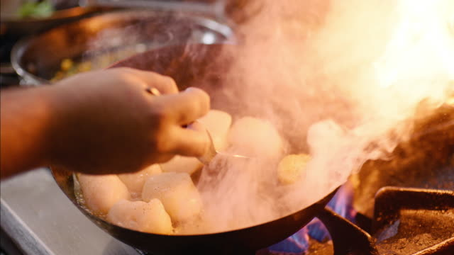 In restaurant kitchen, gourmet chef turns scallops over on skillet over flaming gas stove top in slow motion