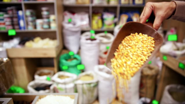 In the grocery. Taking corn grains from sack