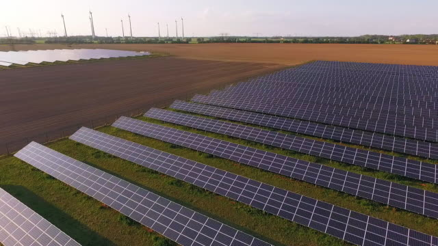 In this aerial view the sun sets over a field of solar energy panels as wind turbines spin nearby on September 4 2015 near Nauen Germany Germany has...