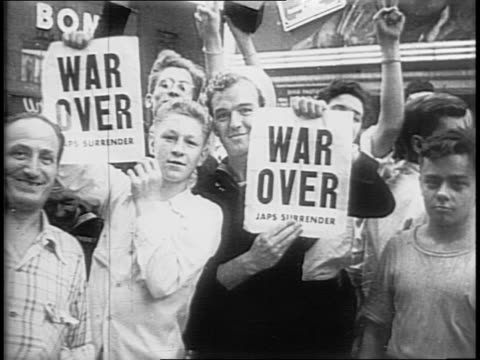 In Times Square a sign reads that Truman announces Japanese surrender / people have filled the streets and are celebrating waving to camera / women...