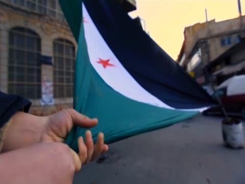 In Zabadani main square a child holds the Syrian Independence flag