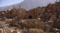 Inca ruins cast shadows on a dusty plateau.