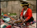 Inca woman in traditional clothes weaving colourful materials, Peru