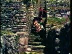 1953 WS Incan ancient structures on side of the Andes, Group of Llamas walking across grassy hill, Men walk up step ancient staircase dressed in Peruvian garb / Peru / AUDIO