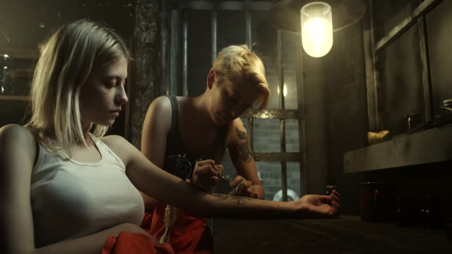 Incarcerated tattoo master tattooing blonde women at prison