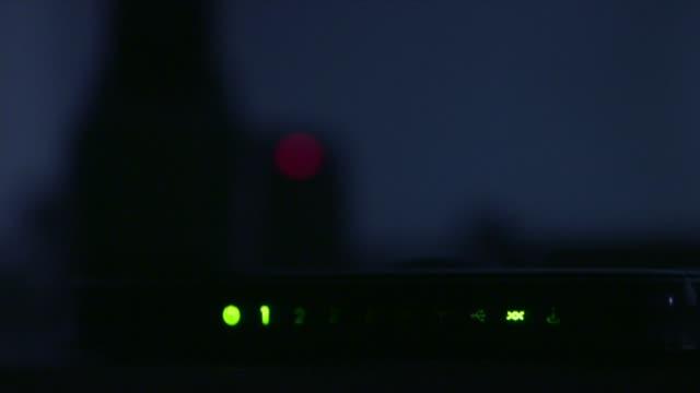 Increase in online sex crimes committed against children T02061617 / TX Closeup laptop litup in dark room Modem lights flashing in dark Closeup hands...