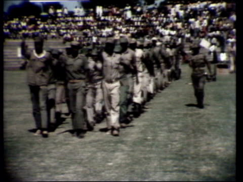 Independence ceremony DAY Crowd in stadium Marching soldiers Prisoners and police as arrested people board police vans Van along with prisoners