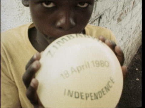 Independence ceremony preparations Young boy blows up baloon with logo 'Zimbabwe Independence 18 April 1980'