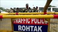Indian authorities ramp up security by warning residents to stay indoors and setting up road blocks in the northern city of Rohtak as an Indian guru...
