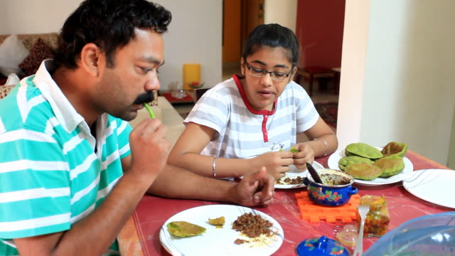 Indian father and daughter having breakfast together