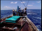 Indian fishermen on boat fish for tuna and fling fish into middle of boat, Indian Ocean