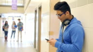 Indian high school male student texting on smart phone while standing in hallway