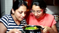 Indian housewives women smelling and appreciating food cooked by them
