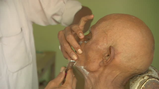 Indian man having his face shaved by barber in India
