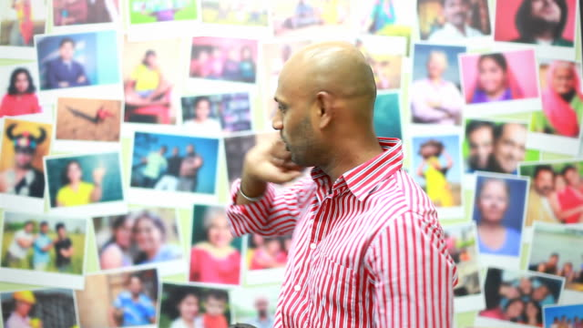 Indian man showing photographs on the Wall and explaining