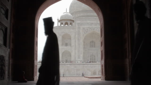 Indian men walk through a mosque doorway, Taj Mahal in the background