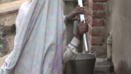 Indian women pumping out water