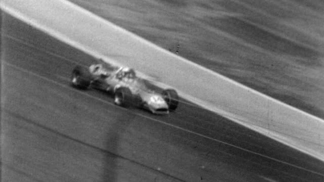 Indianapolis 500 / mid race cars going around the track passing a huge blurred crowd / car spins / Parnelli Jones' car speeds eventually drops out of...