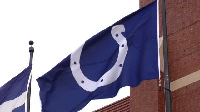 Indianapolis Colts flag blows in the wind Shot in front of Lucas Oil Stadium