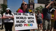 A person holds a sign reading 'Now fill the world with music love and pride' Members of the LGBTQ community and their allies gather to rally at...