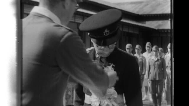 Indigenous civilians watch as a Japanese Army officer attaches the badge of Honorary Counselor on the chest of the Sultan of Miri and then the sultan...
