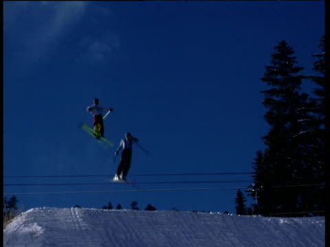 Individual skiers perform acrobatic jumps in air in succession from ski-jump. Fir tree to right of frame