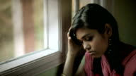 Indoor close-up of sad Asian teenager girl sitting near window.