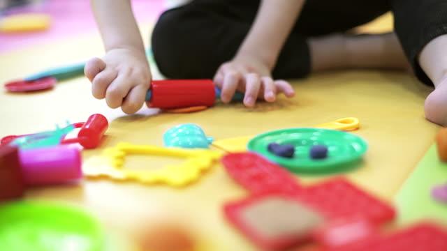 Inomhus porträtt av unga kaukasiska barn leker med spela degen med fokus på hans hand.