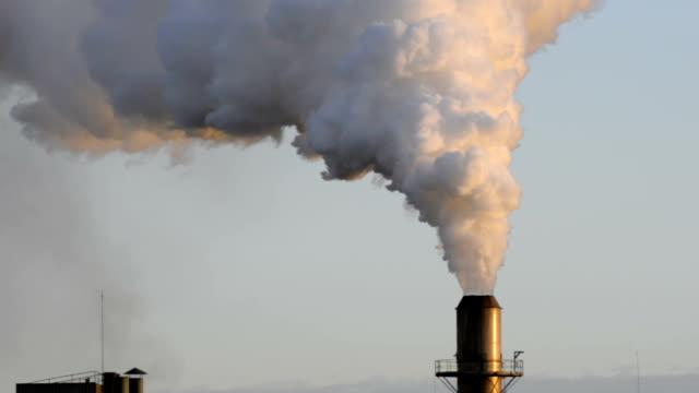 Industrial chimney exhaling smoke at sunset