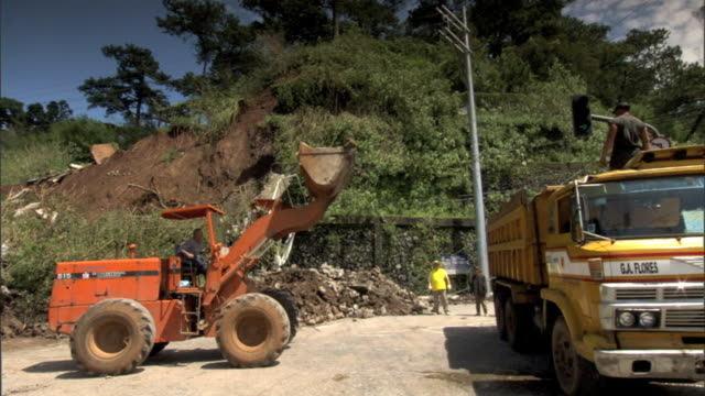 WS Industrial front end loader w/ bucket raised pulling up to above side of dump truck ZI MS Bucket tilting downward dumping rocks into truck...