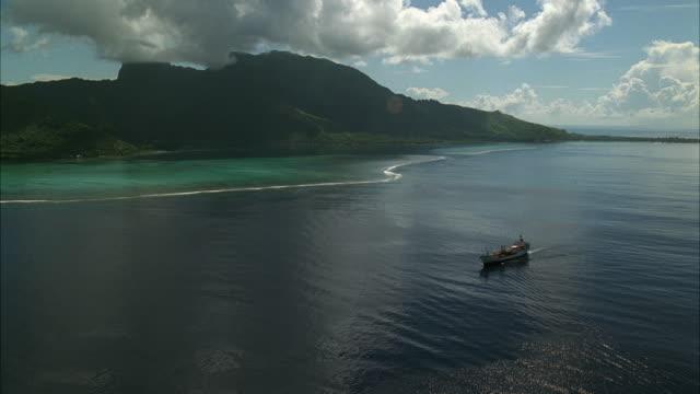 AERIAL WS Industrial Ship Moving On Ocean Near Mountains / Tahiti, French Polynesia
