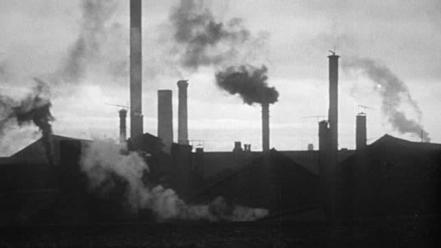 1948 MONTAGE Industrial skyline with smokestacks and workers leaving the factory job for the day / Sheffield, England, United Kingdom