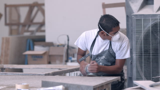 CU industry worker sanding the edge of marble piece and changing out sandpaper of his power sander wearing dust mask and assisted by large fan that clears the air of dust particles  / Thousand Palms, California, USA