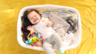 A infant baby lying in a laundry basket filled with clothes.