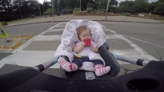 A infant baby riding in a stroller outdoors in a residential area.