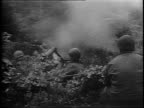 Infantrymen camp behind the front line / soldier shaving next to a clothes line / closeup shots of two men making a fire and cleaning a gun / soldier...