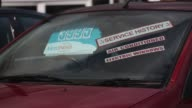 Information stickers and price labels sit in the windows of second hand cars on the forecourt of a used car dealership in LeighonSea UK used car...