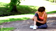Injured fit woman touching her ankle in the park