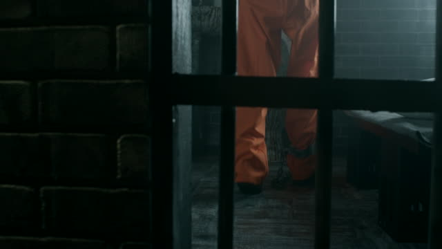 Inmate with shackles on legs walking in prison