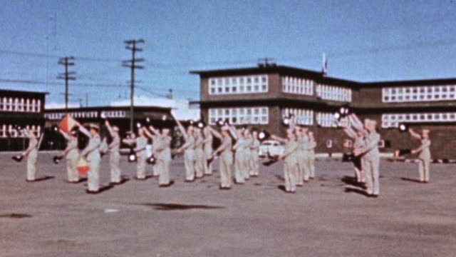 WS Insession class at the Maritime Service Officers' School where officers are standing in formation and practicing signaling with flags / Alameda...