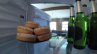 Inside a fridge, a woman decides between beer and doughnuts