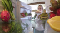 Inside a fridge, a woman takes out an iced cake